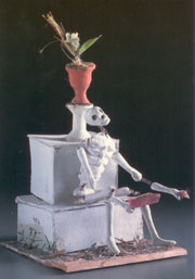Photograph of skeleton holding book.